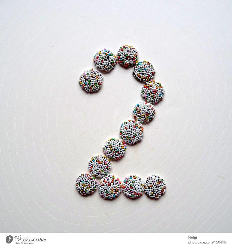 Zahl 2 gelegt aus kleinen Schokoladenbonbons mit bunten Zuckerstreuseln auf weißem Hintergrund Ziffern & Zahlen Adventskalender Bonbon Süßwaren Streusel