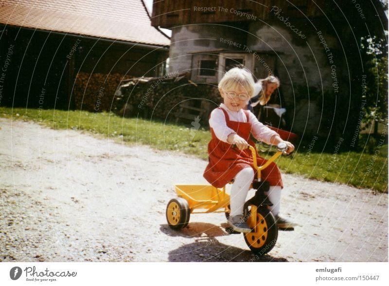 Wheels keep on turning... gelb rot Dreirad Kind blond fahren Bauernhof Hof Brille Kleid Freude Kleinkind Sommer