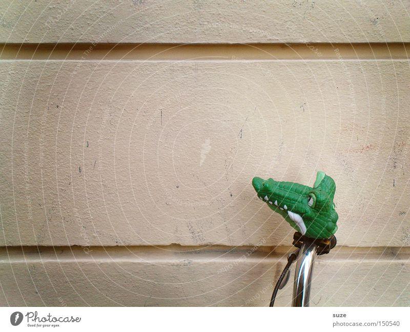 Abgelenkt Fahrrad grün Fahrradlenker Krokodil Wand Fahrradklingel Gummi parken lustig Farbfoto Gedeckte Farben Außenaufnahme Menschenleer Textfreiraum links