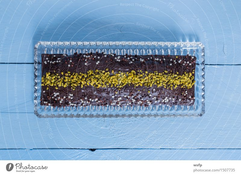 Schokoladenkuchen mit Pistazien auf blauem Holz Kuchen Dessert Backwaren klassisch Tortenguss Biskuit Holztisch Landhaus rustikal Vogelperspektive Süßwaren süß