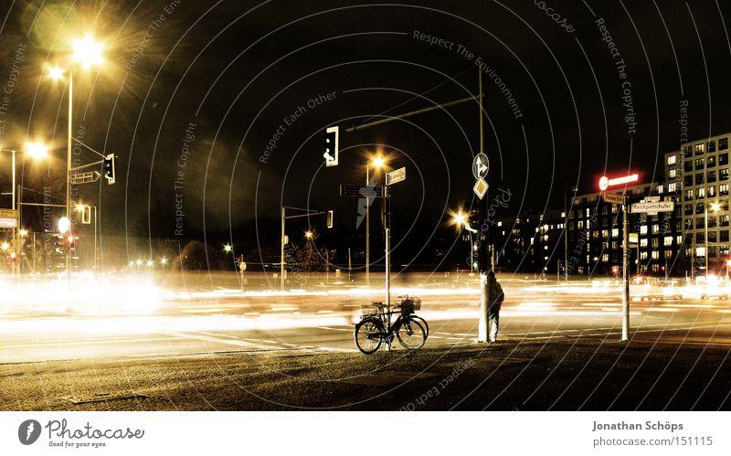 Mann steht neben Fahrrad nachts an Berliner Straßenkreuzung mit Verkehr Stadt Verkehrswege Wegkreuzung Ampel PKW Bewegung Geschwindigkeit Nachtaufnahme KFZ
