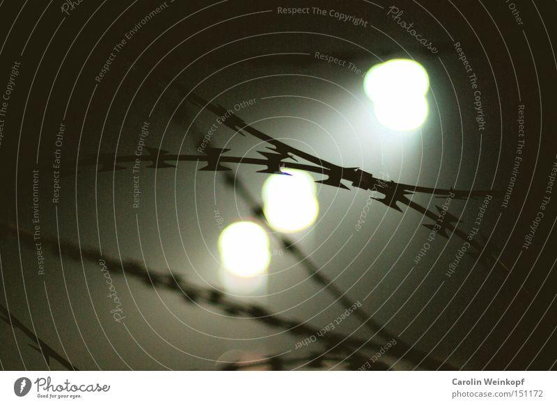 Drüben. Angst Grenze Zaun Panik Scheinwerfer Stacheldraht Stacheldrahtzaun