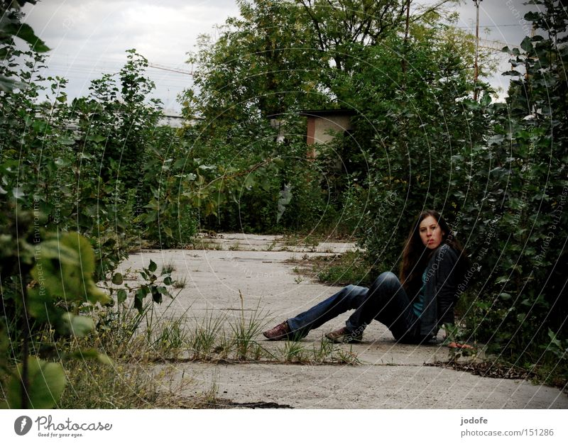 lonely Frau Mensch sitzen Natur Beton Bodenbelag Wege & Pfade Sträucher Misstrauen Angst feminin schäbig Straße Potsdam Verkehrswege Schwäche verwildert