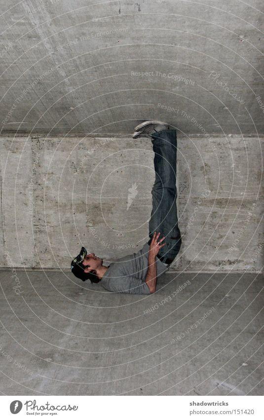 Statik Mann grau Kraft Beton Baustelle Neigung Jeanshose Konstruktion Säule schwer Akrobatik drücken zwischen Betonwand Zwischenraum