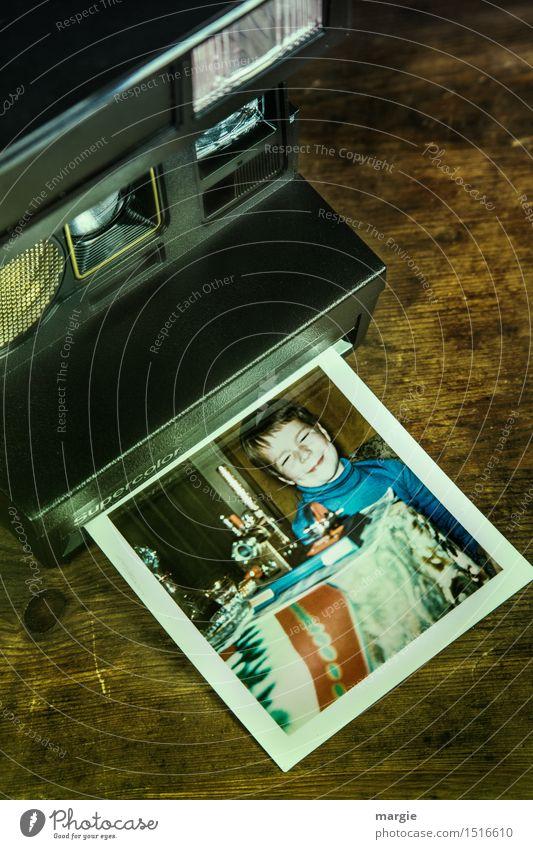 Eine alte analoge Kamera mit dem Foto eines kleinen Jungen der sich zu Weihnachten über seine Geschenke freut Spielen Mensch maskulin Kind 1 3-8 Jahre Kindheit