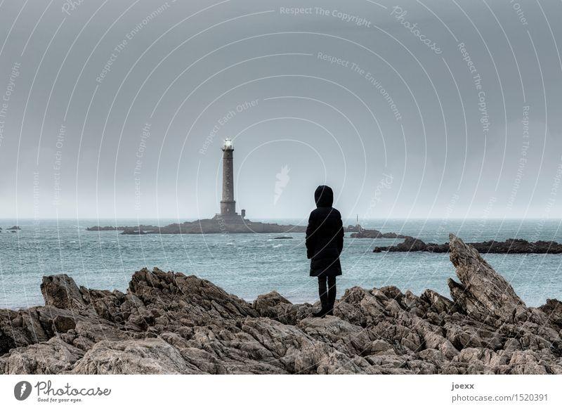 Frau im Mantel mit Kaputze beobachtet entfernten Leuchtturm im Meer Felsen Küste Person Felsig schroff rauh düster Hoffnung Licht Sehnsucht beobachten Wasser