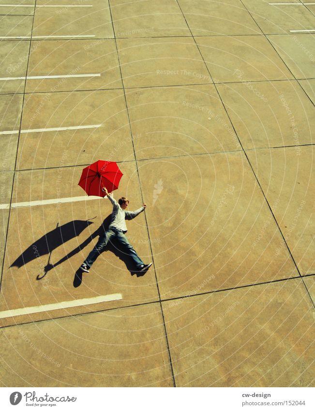 EIN FOTO VON DER STANGE Mensch Mann rot Freude Spielen maskulin Beton stehen liegen Regenschirm Sonnenschirm Verkehrswege Schönes Wetter Schirm Parkplatz