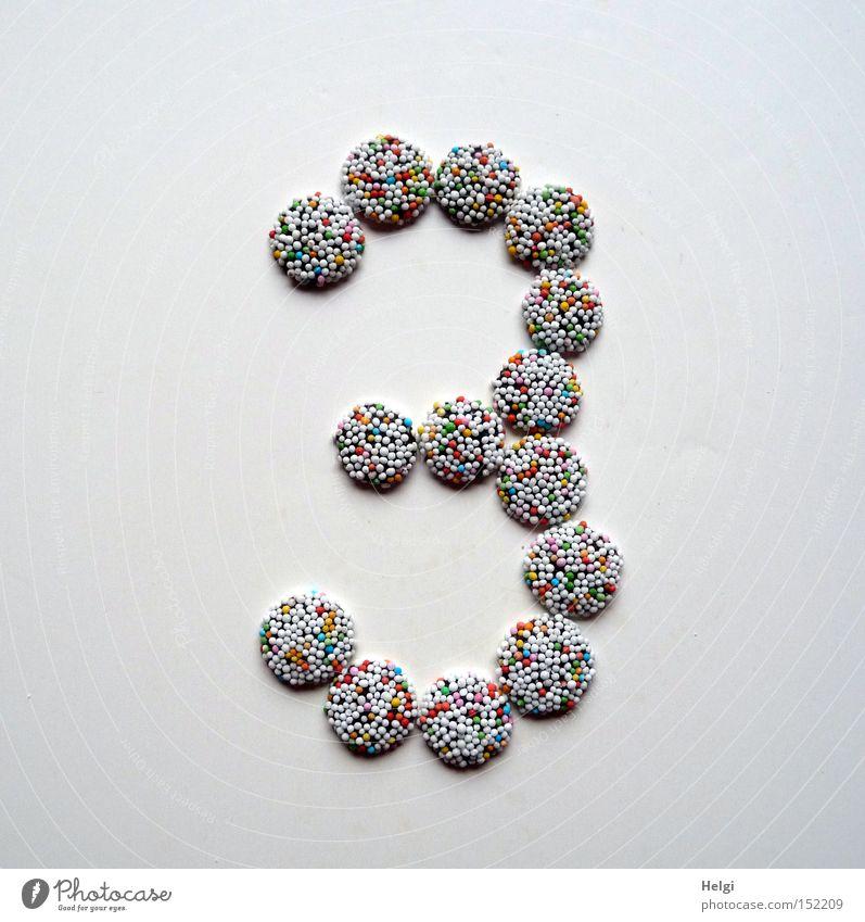 Zahl 3 gelegt aus kleinen Schokoladenbonbons mit bunten Zuckerstreuseln auf weißem Hintergrund Ziffern & Zahlen Adventskalender Bonbon Süßwaren Streusel