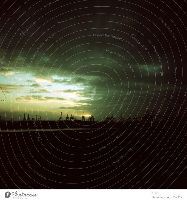 Die Sonne am Horizont schwarz Wolken dunkel Hamburg Industrie Hafen Kran