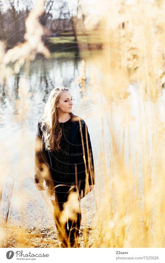 Herbsttag Lifestyle elegant feminin Junge Frau Jugendliche 18-30 Jahre Erwachsene Landschaft Sonne Schönes Wetter Sträucher Schilfrohr Seeufer Mantel blond