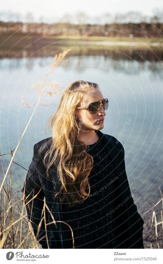 Nochmal Sonne tanken Lifestyle elegant Stil Junge Frau Jugendliche 18-30 Jahre Erwachsene Natur Landschaft Schilfrohr Seeufer Mode Mantel Sonnenbrille blond