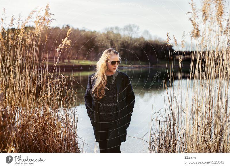 Ein Tag am See Lifestyle elegant Stil Sonne Junge Frau Jugendliche 18-30 Jahre Erwachsene Landschaft Frühling Sträucher Seeufer Mode Mantel Sonnenbrille brünett