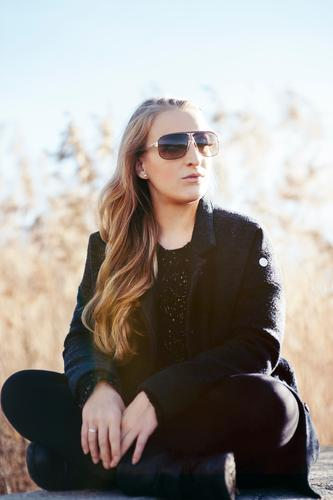 Nochmal Sonne tanken Lifestyle elegant Stil Junge Frau Jugendliche Natur Landschaft Herbst Schönes Wetter Schilfrohr Mode Mantel Sonnenbrille blond langhaarig