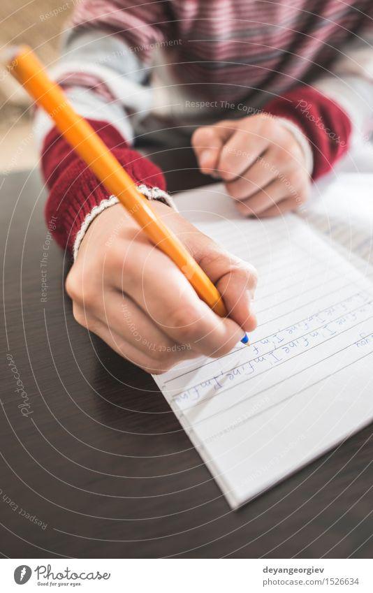 Kind schreibt in ein Notizbuch Schule Klassenraum Junge Kindheit Hand Buch Papier Schreibstift schreiben weiß schreibend Bildung Hausaufgabe Notebook Bleistift
