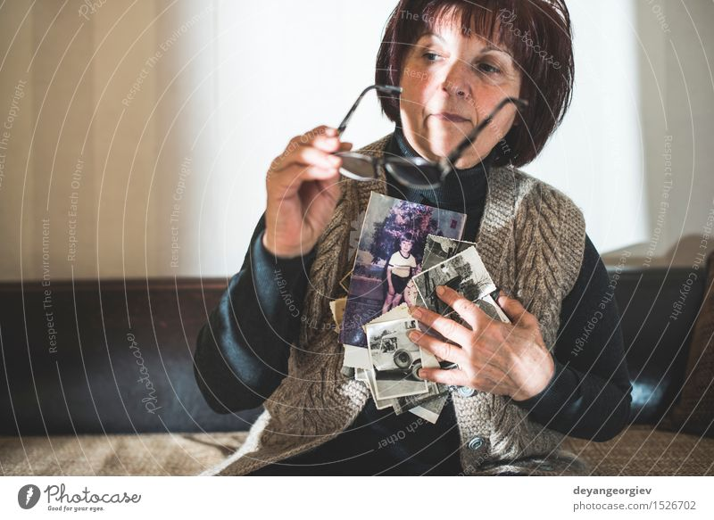 Ältere Frau, die alte Fotos aufpasst Lifestyle Tisch Mensch Erwachsene Mutter Großmutter Familie & Verwandtschaft Freundschaft Hand beobachten sitzen