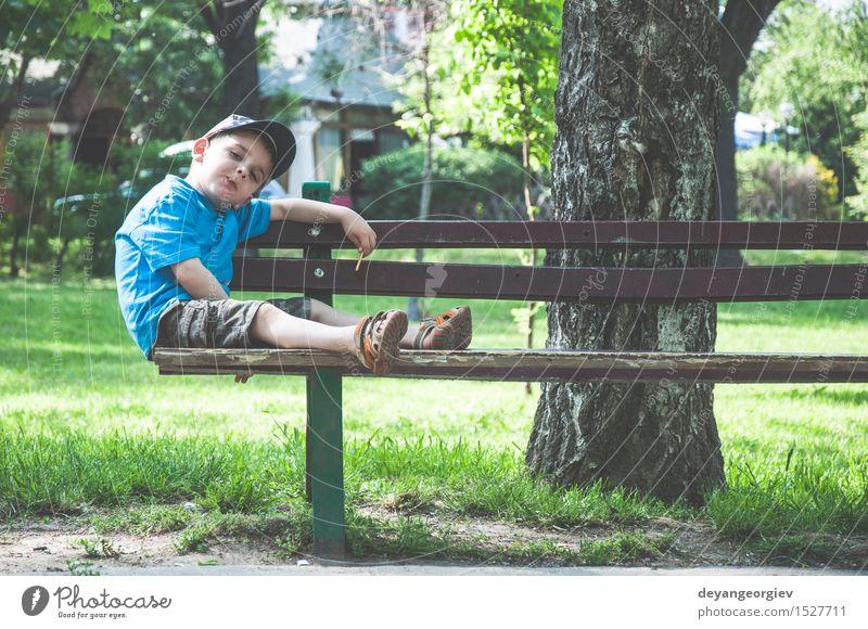 Kleiner Junge auf einer Bank im Park Lifestyle Freude Glück Sommer Kind Mensch Kindheit Natur Herbst sitzen klein niedlich essen jung Kaukasier Außenaufnahme