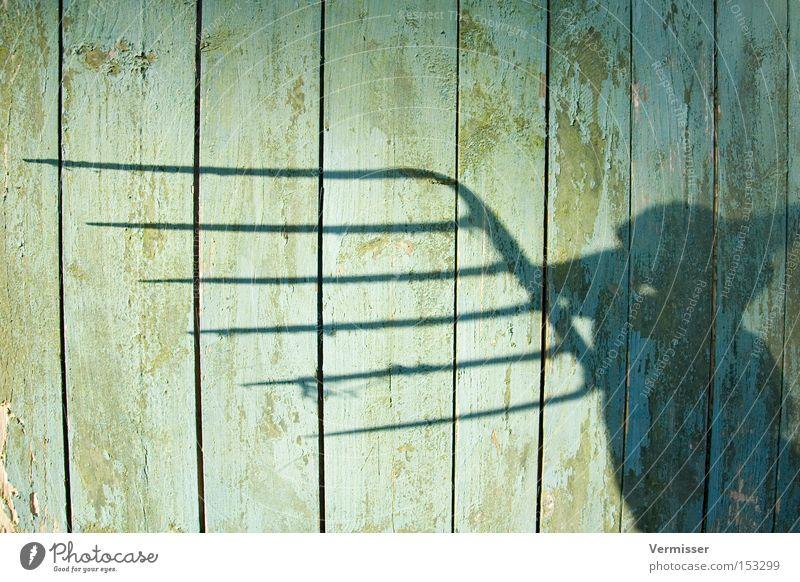 Bauernopfer. Holz Metall Forke Farbe abblättern Schatten blau bedrohlich Holzwand Arme Hand Wut Ärger Kraft