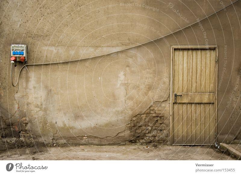 Unter Strom. Fassade grau Tür alt verfallen Elektrizität Eingang Ruine Industriefotografie Kabel Steckdose trist Vergänglichkeit