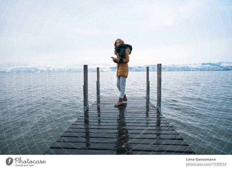 Junge Frau mit Smartphone auf einem winterlichen Steg Himmel Wasser Erholung Landschaft Winter Berge u. Gebirge Schnee Gesundheit Holz See Zufriedenheit Nebel