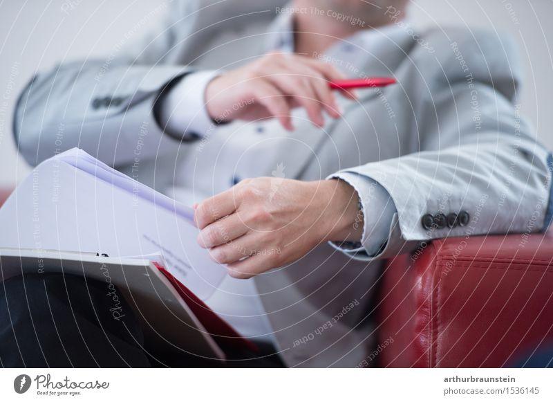 Geschäftsmann im Anzug mit Unterlagen in der Hand auf roter Couch Berufsausbildung Studium lernen Büroarbeit Arbeitsplatz Wirtschaft Dienstleistungsgewerbe