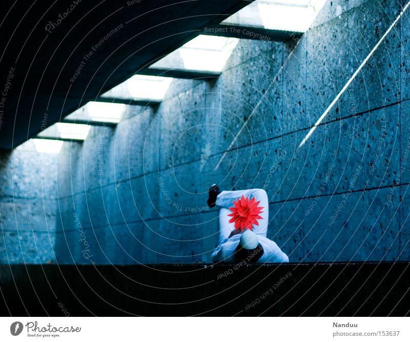 Man könnte die Augen öffnen, muss aber nicht. Mensch weiß Blume blau rot kalt Beton Frieden liegen Maske festhalten Tunnel skurril bequem friedlich Lichtstrahl