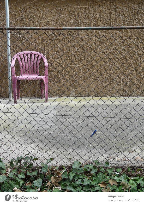 Wäscheklammerattentat Hinterhof Stuhl Maschendraht Maschendrahtzaun Efeu Wäscheklammern braun grau Vorgarten leer Einsamkeit Gartenstuhl Langeweile