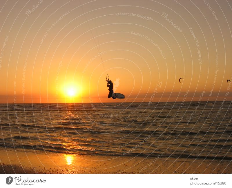 Nightsurfing Kitesurfer Sonnenuntergang Meer Wellen Strand Sport fliegen Abend
