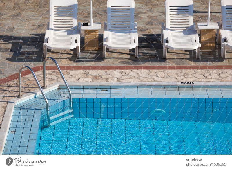 Sauberer blauer Swimmingpool mit klarem Wasser und Sonnenliegen drum herum an einem heißen Sommermorgen. Lifestyle schön Erholung Spa Schwimmbad