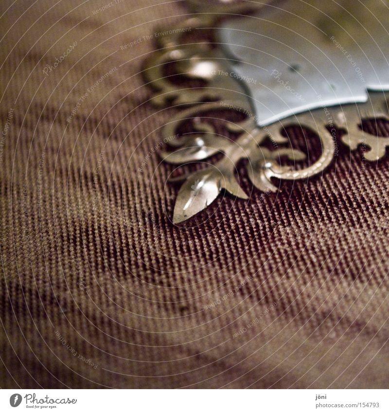 Relikte aus vergangenen Zeiten Wappen Schnörkel Stoff alt Bucheinband Staub Verfall Antiquität Mangel Erinnerung früher Vergänglichkeit Metall verstaubt selten