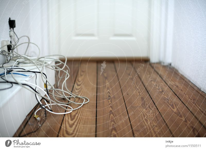 Kabelsalat im Flur Häusliches Leben Holzfußboden Holztür Telekommunikation Menschenleer chaotisch unordentlich durcheinander Farbfoto Innenaufnahme Nahaufnahme
