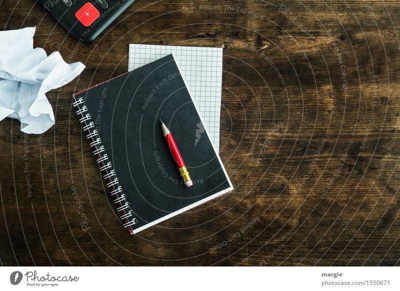 """Ein roter Bleistift auf einem schwarzen Heft, ein karierter Zettel, ein weißes zerknülltes Blatt mit einem roten """"+"""" auf einem alten Schreibtisch Schule"""