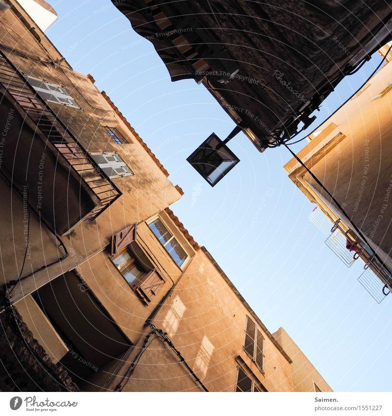 UrbanFrogArt I Dorf Kleinstadt Altstadt Haus Gebäude Mauer Wand Fassade Balkon alt dreckig blau braun Urlaubsstimmung Reisefotografie Straßenbeleuchtung Fenster