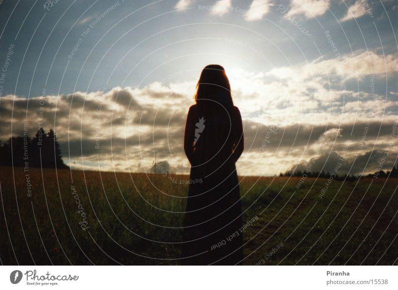 Mädchensilhouette vor Sonnenuntergang Wolken Wiese