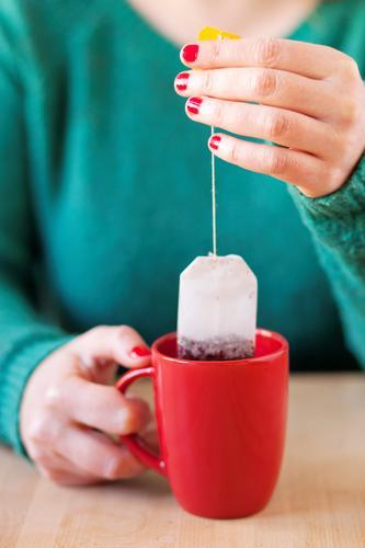 Tee trinken Mensch Frau grün Gesunde Ernährung Hand Erholung rot ruhig Erwachsene Leben feminin Gesundheit Zufriedenheit Häusliches Leben Tisch Finger