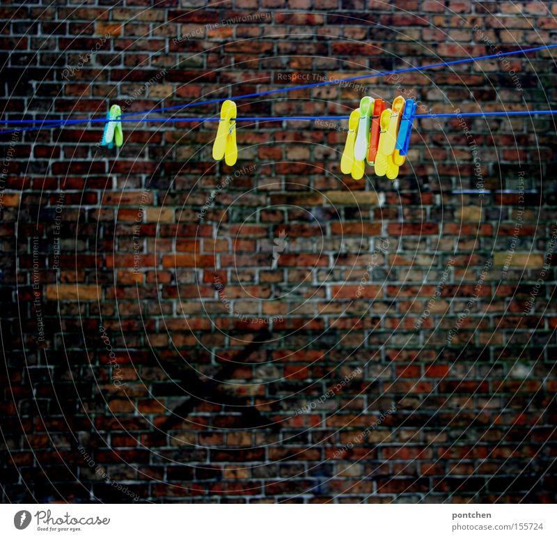 Bunte Wäscheklammern hängen an einer  Wäscheleine in einem  Hinterhof. Backsteinwand Haus Mauer Wand festhalten trist Hof Haushalt leer trocknen aufhängen
