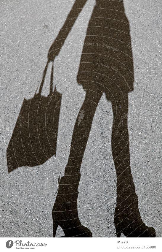 Shoppingtour Frau schwarz Straße grau Erwachsene Beine Schatten Schuhe kaufen Asphalt Lebensfreude Kies Tüte unterwegs Mensch Konsum