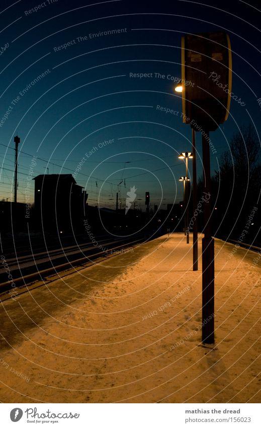 NÄCHTLICHES WARTEN Bahnsteig Gleise Hochspannungsleitung Kabel Laterne Kunstlicht Schnee Dämmerung blau Haus Silhouette Menschenleer Einsamkeit ruhig Stadt