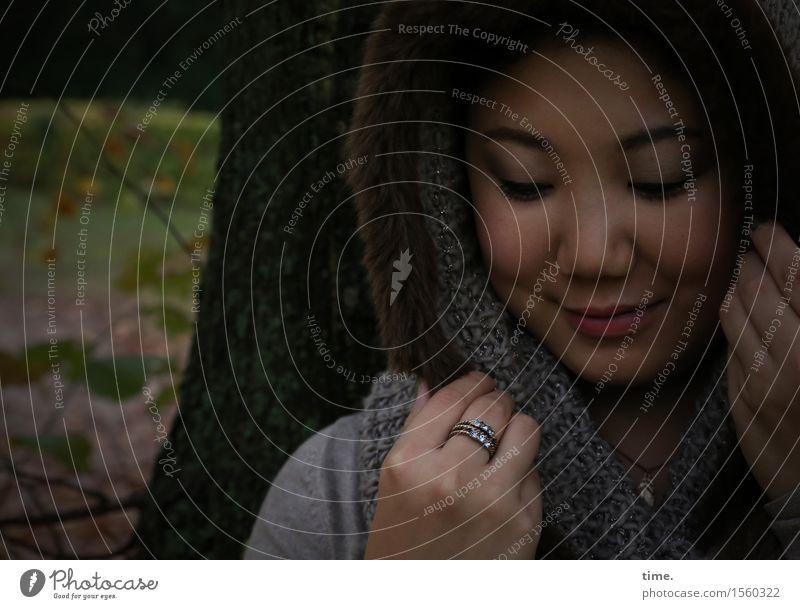 . feminin 1 Mensch Park Mantel Kapuze Ring Schal schwarzhaarig langhaarig beobachten Lächeln Blick träumen warten schön Zufriedenheit Lebensfreude selbstbewußt