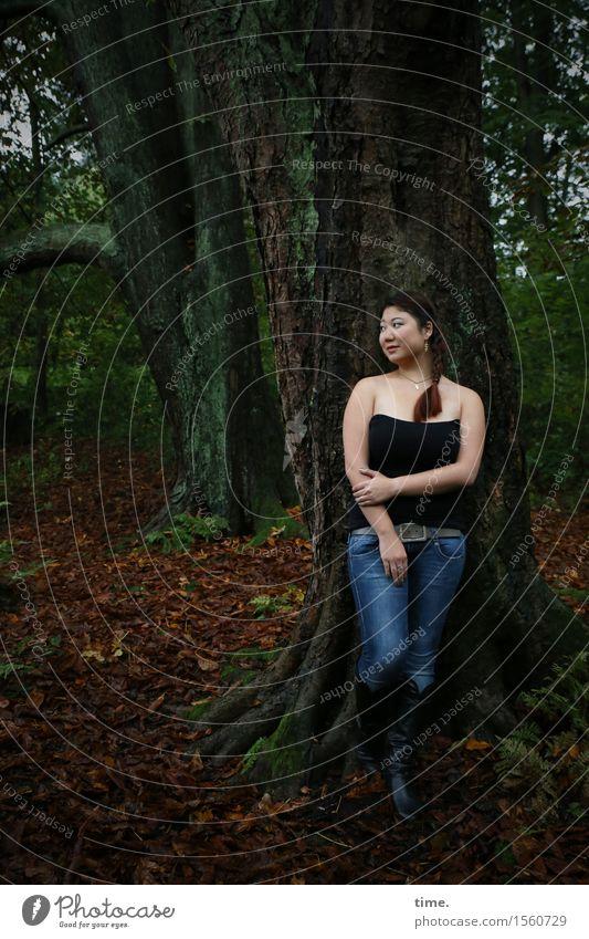 . feminin 1 Mensch Herbst Baum Wald Hemd Jeanshose schwarzhaarig Zopf beobachten Lächeln Blick stehen warten dunkel schön Zufriedenheit Lebensfreude Wachsamkeit