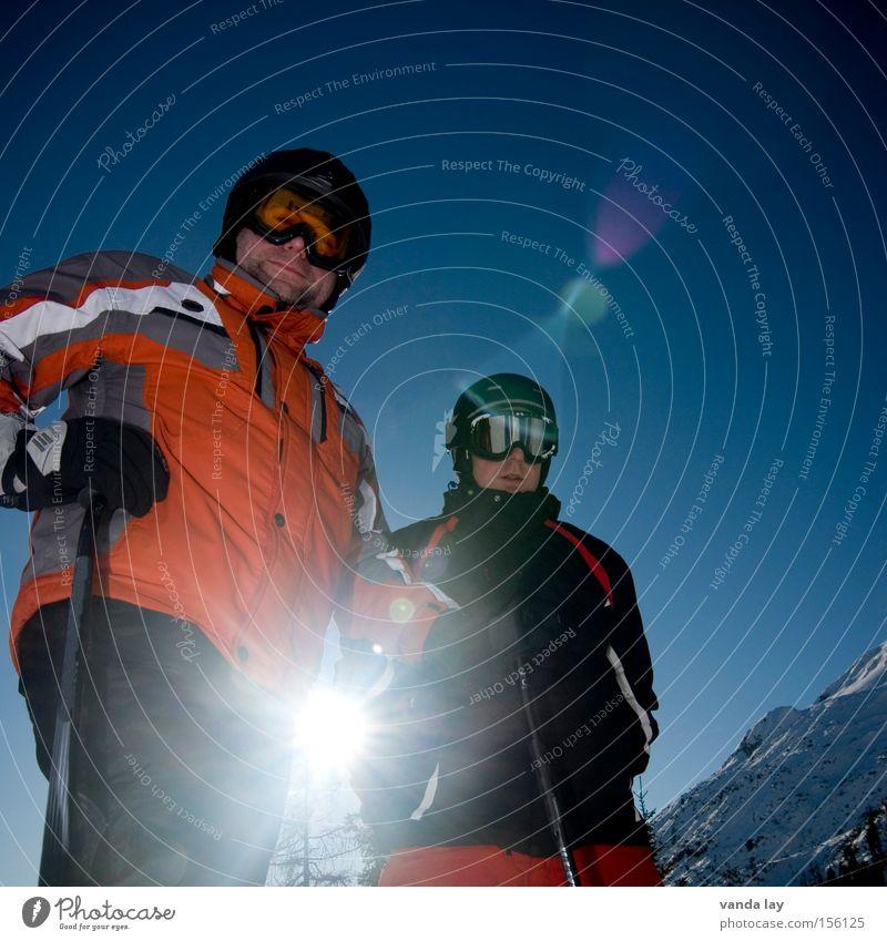 Skihasen Skifahrer Skifahren Skier Sport Wintersport Mann Sportler kalt Helm Brille Freundschaft 2 Schnee Gipfel Blende Blendenfleck stehen Himmel blau