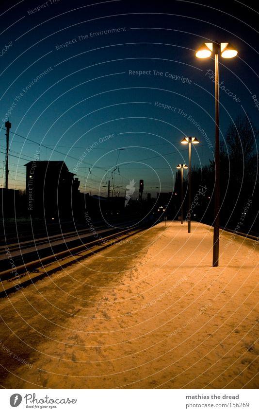 NÄCHTLICHES WARTEN PART II Bahnsteig Gleise Kabel Laterne Kunstlicht Schnee Dämmerung blau Haus Silhouette Menschenleer Einsamkeit ruhig Stadt Bahnhof