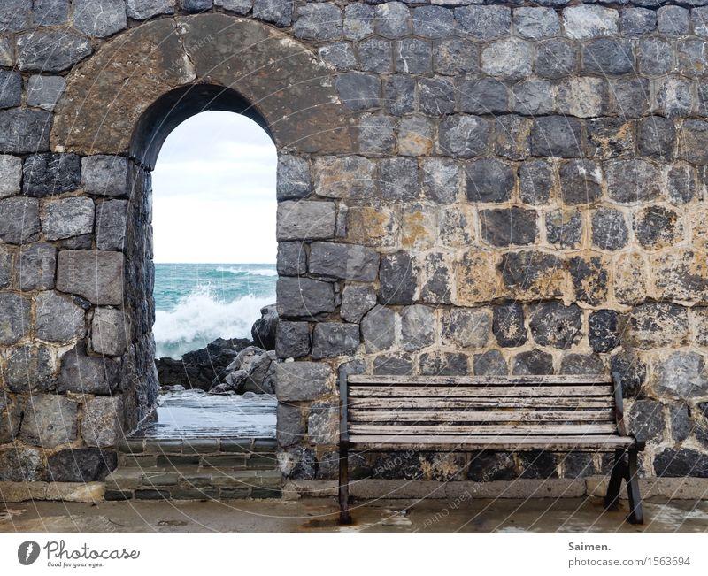 Bank am Meer vor Mauer Ozean Sitzbank Felsen Steine Stadtmauer Italien Mittelmeer Wellen Brandung Detail Küste Gischt Natur nass Farbfoto Strand Himmel