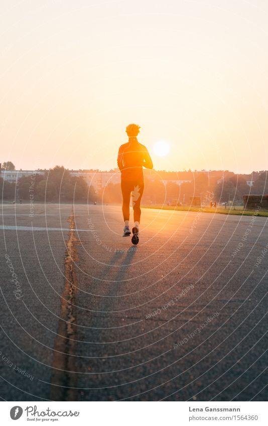 Frau joggt in einen Sonnenaufgang Mensch Frau Jugendliche Sommer Sonne Erholung 18-30 Jahre Erwachsene Straße feminin Sport Gesundheit Zufriedenheit glänzend frei leuchten
