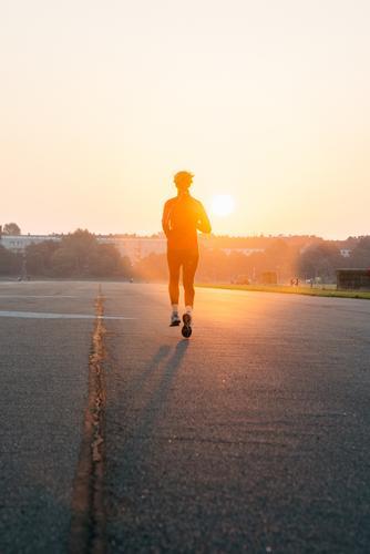 Frau joggt in einen Sonnenaufgang Mensch Jugendliche Sommer Erholung 18-30 Jahre Erwachsene Straße feminin Sport Gesundheit Zufriedenheit glänzend frei leuchten