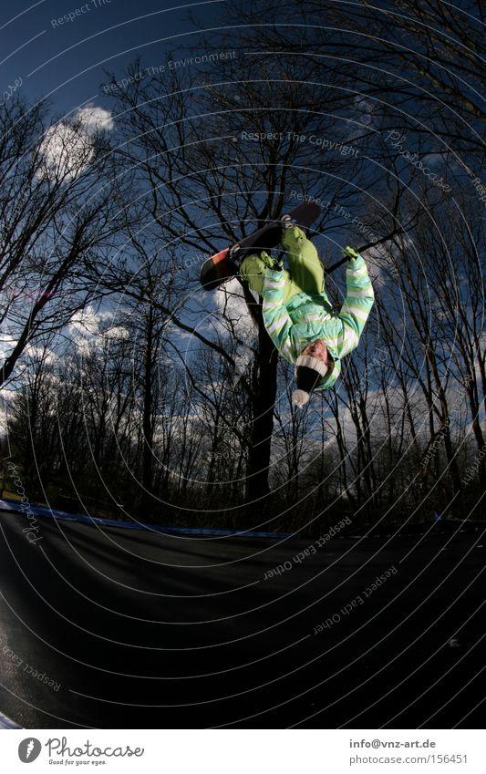 Training for winter Trampolin Snowboard Trick springen Himmel Fischauge Baum blau grün Rückwärtssalto Salto Mütze Jacke Hose Winter Sommer Extremsport dunkel
