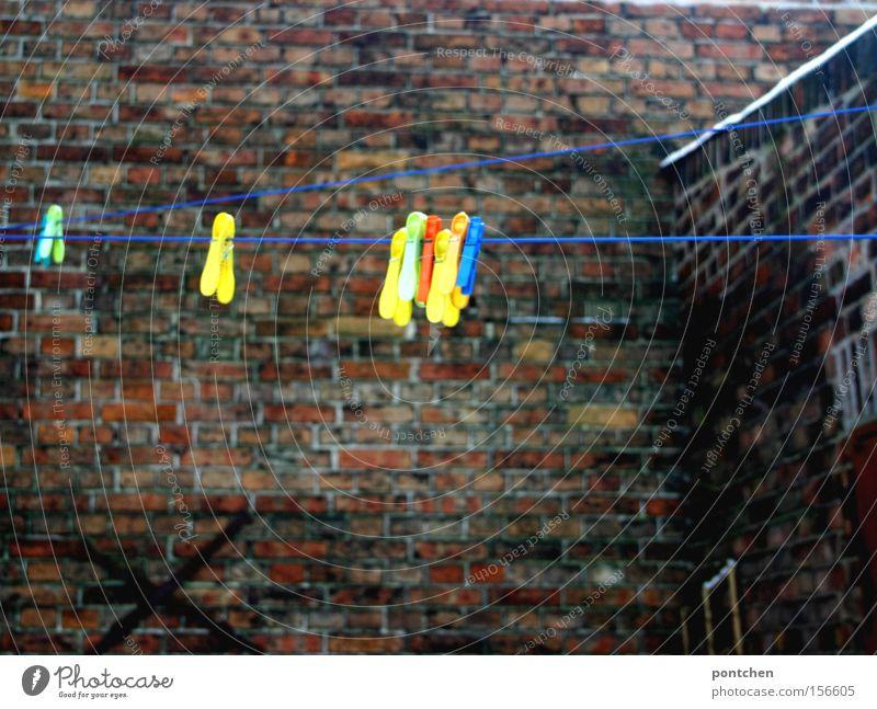 Bunte Wäscheklammern hängen an einer Wäscheleine in einem Hinterhof. Haushalt Hof Backstein Mauer trist leer trocknen aufhängen Deutschland Haushaltsware