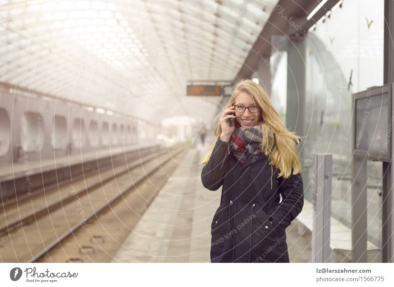 Junge Frau im schwarzen Mantel unter Verwendung des Handys Mensch Jugendliche Winter 18-30 Jahre Gesicht Erwachsene feminin Glück Verkehr blond authentisch