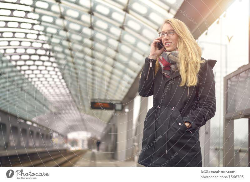 Blonde Frau mit Handy an der Bahnstation Mensch Jugendliche Winter 18-30 Jahre Gesicht Erwachsene feminin Glück Verkehr Textfreiraum blond authentisch