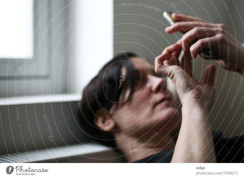 Spieltrieb - immer on Mensch Frau Hand Gesicht Erwachsene Leben Lifestyle Spielen liegen Freizeit & Hobby Internet Handy Surfen online PDA bequem