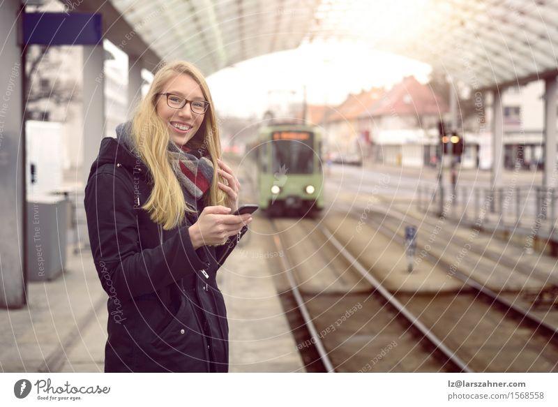 Lächelnde junge Frau in schwarzem Mantel, blonden Haaren und Brille steht am Bahnhof Glück Ferien & Urlaub & Reisen Winter Telefon Erwachsene Verkehr Eisenbahn